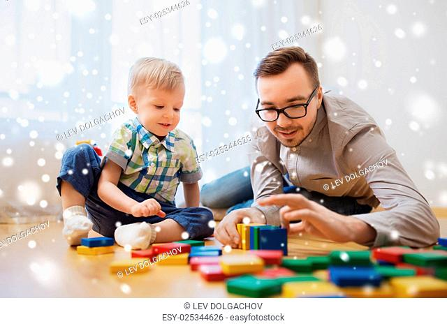 family, childhood, creativity, activity and people concept - happy father and little son playing with toy blocks at home over snow