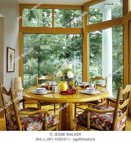EATING AREAS: Family room eating area, large windows look onto a wooded yard, light honey colored wood French Provincial style round table and chairs