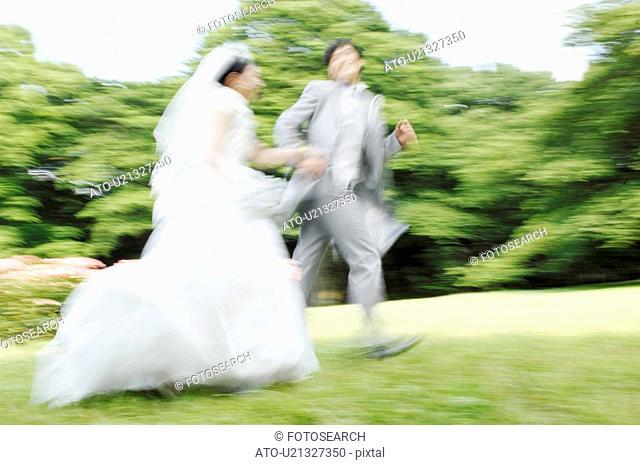 Bridal couple running in garden