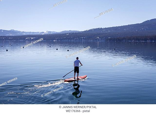 Young man seen from behind as he standup paddles at Lake Tahoe
