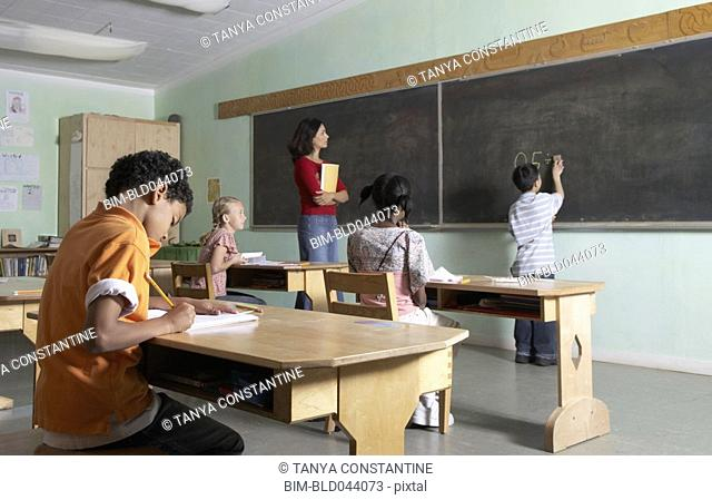 Asian boy writing on blackboard