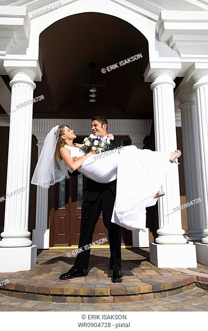 Young man carrying his bride in his arms in front of a building