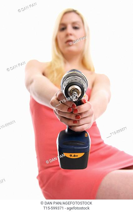 Young girl in her 20's holding a power tool/ drill in her hand pointing to the camera