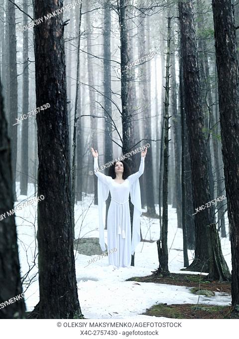 Woman in white dress standing in a middle of a forest with her arms raised to the sky. Spiritual concept. Wintertime outdoor scenery