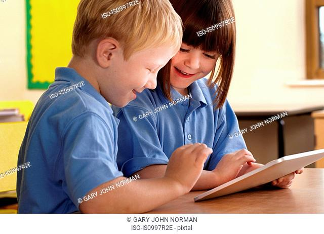 Two school children using computer notebook in classroom
