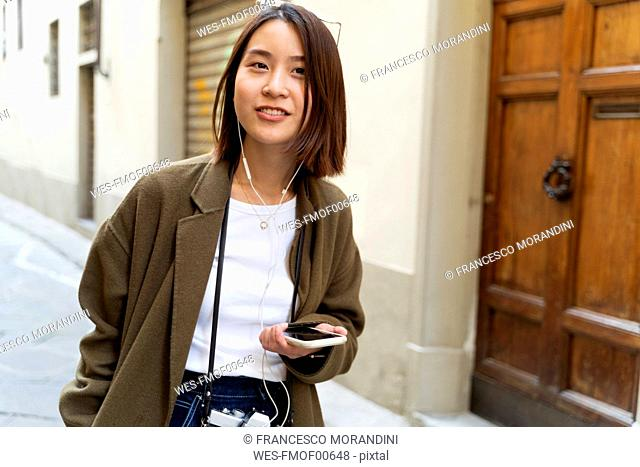 Italy, Florence, young woman with earphones and cell phone in an alley