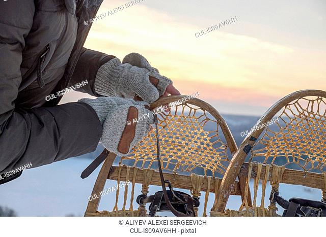 Close up of mans gloved hands preparing snow shoes, Ural, Russia