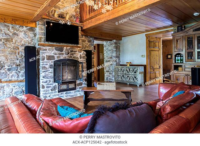 Reddish-burgundy leather sofas with wooden bench style coffee table in living room with natural stone fireplace with wrought iron doors inside an old 1826...