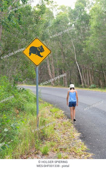 Australia, New South Wales, Pottsville, roadsign with a koala bear and girl walking along road in Pottsville Environmental Park