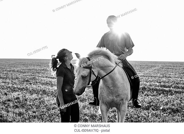 B&W image of woman chatting with man riding grey horse in field