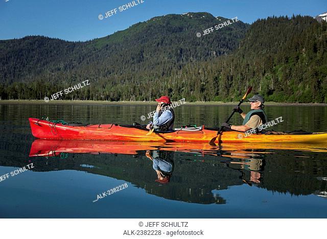 Woman talking on smart phone while kayaking in Halibut Cove Lagoon area in Kachemak Bay State Park, Alaska, Summer
