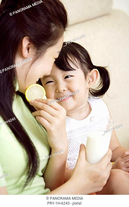 Mother and daughter with glass of milk