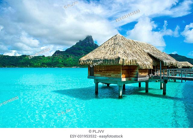 Luxury overwater thatched roof bungalow in a honeymoon vacation resort in the clear blue lagoon with a view on the tropical island of Bora Bora, near Tahiti