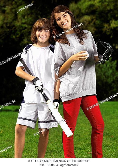 Portrait of two happy smiling children, brother and sister, 10 and 13, practicing baseball, active summer outdoor lifestyle