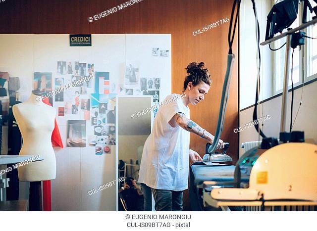 Fashion designer ironing in her work studio