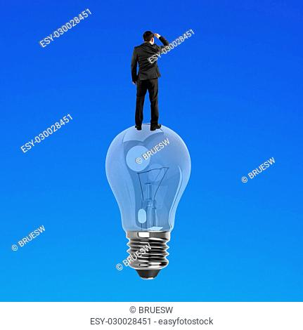 Businessman standing on light bulb, isolated on blue background