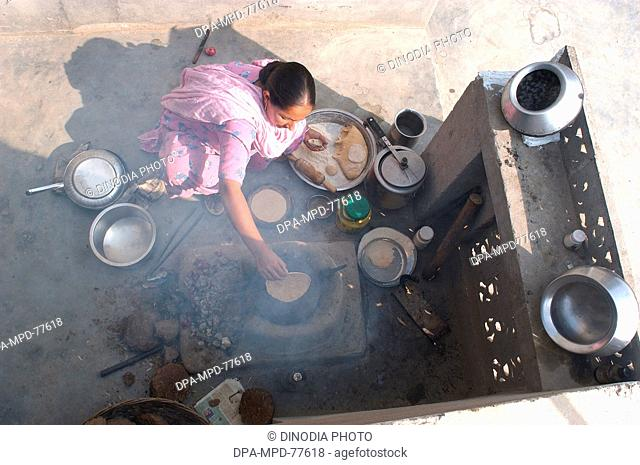 A Punjaban (word used to describe Punjabi woman) making rotis on the clay choolah in the open kitchen at home ; in Doulo Nangal ; a village near the Beas river...