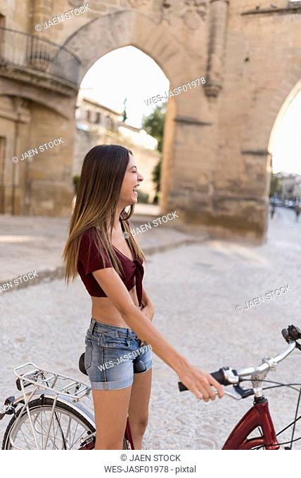 Spain, Baeza, laughing young woman with bicycle in the city