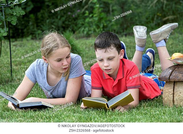 Boy and girl twelve years reading books on nature