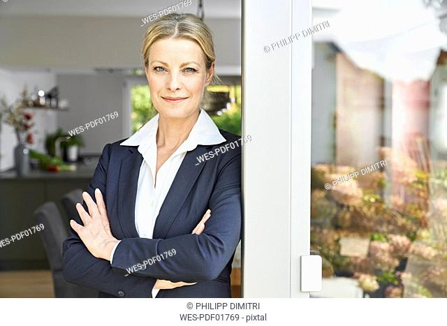 Portrait of confident businesswoman leaning against French door at home