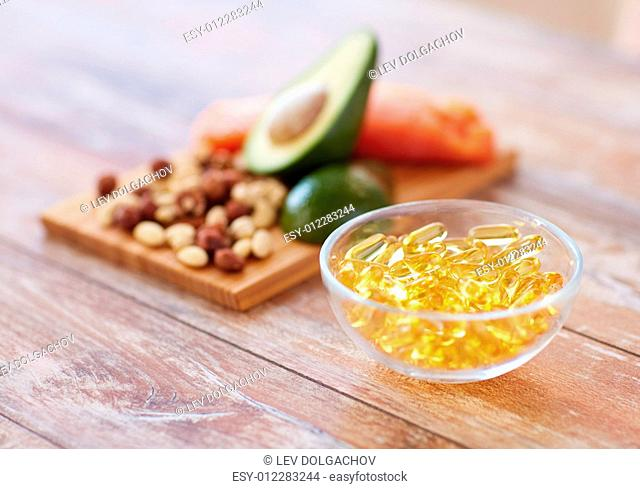 healthy eating, diet and omega 3 nutritional supplements concept - close up of cold liver oil capsules in glass bowl and food on table