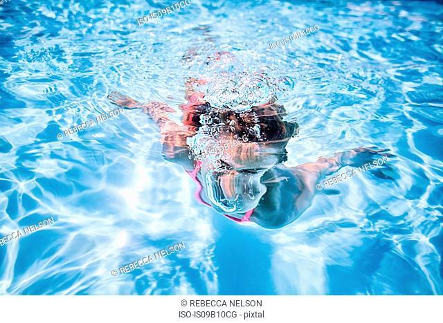 Girl swimming underwater in sunlit swimming pool