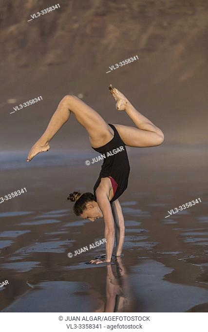 Side view of young fit woman showing beautiful handstand asana on wet sandy beach in sunlight