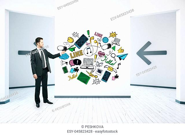 Young caucasian businessman in room with creative social media sketch on wall. Communication concept. 3D Rendering