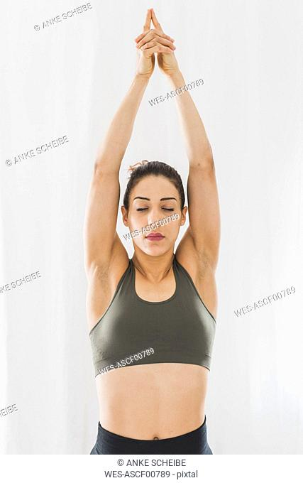Woman practicing yoga raising her arms