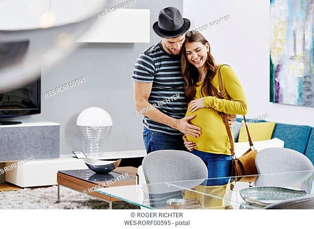 Couple with pregnant woman in furniture store looking at dining table