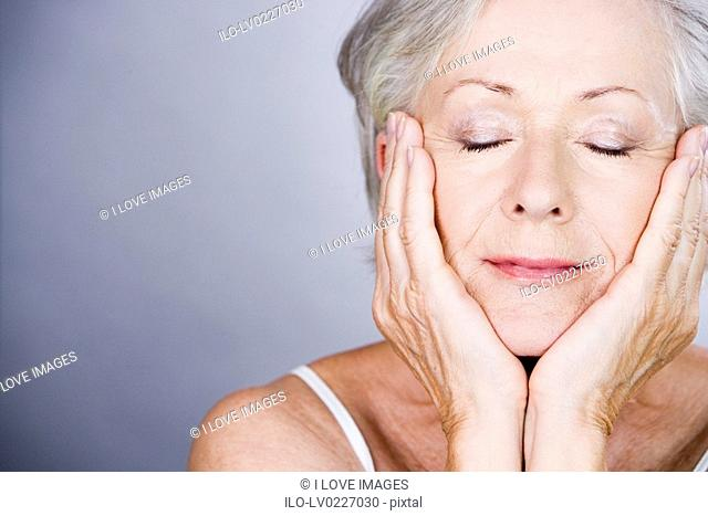 A senior woman with head resting in hands