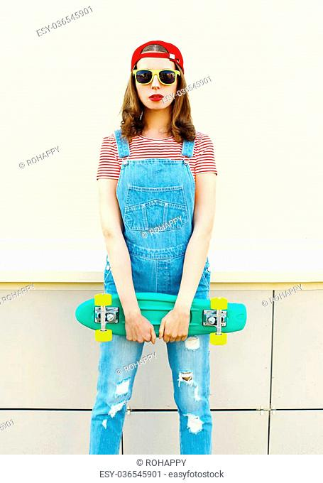 Fashion portrait pretty cool girl with skateboard over white background