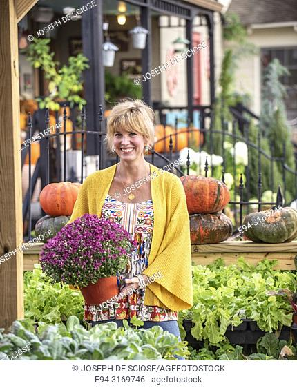 A pretty 42 year old blond woman shopping at a garden store holding a large potted chrysanthemum plant