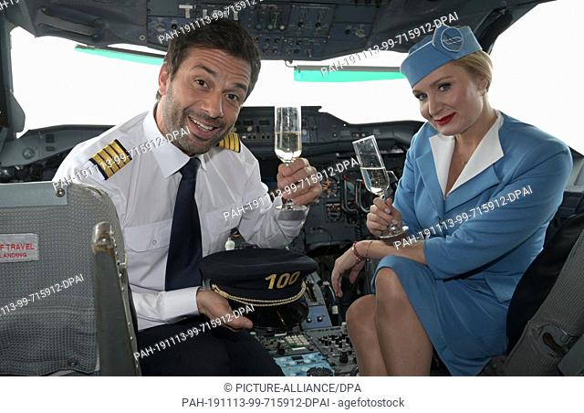 13 November 2019, North Rhine-Westphalia, Cologne: The actors Kai Schumann (l) and Janine Kunze (r) sit in the cockpit of an airplane while filming the 100th...