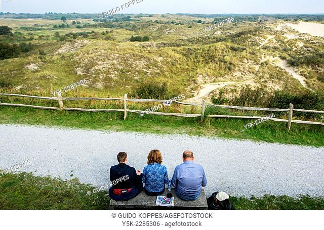Schiermonnikoog, Netherlands. Three middle aged wanderers taking a break on a bench, during a strawl through the island dunes