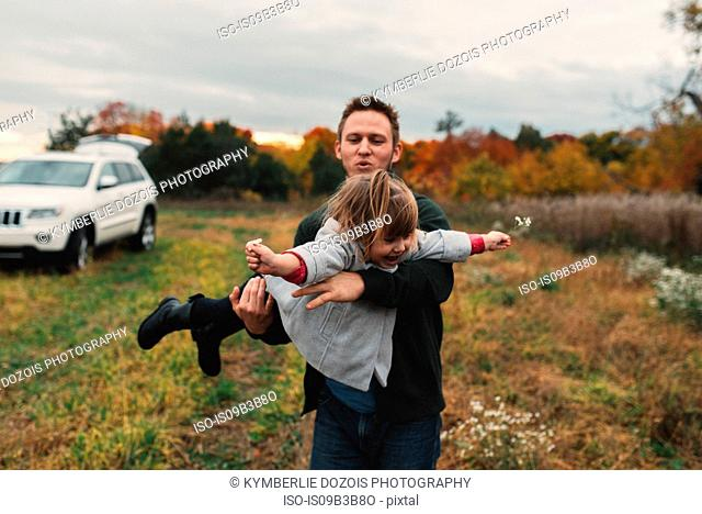 Mid adult man playing with toddler daughter in field