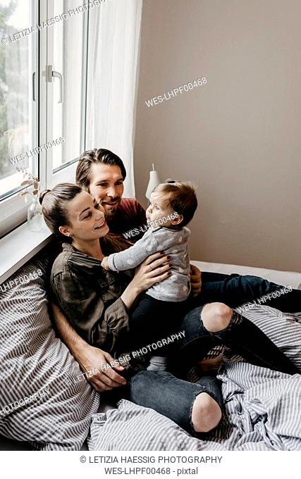 Happy family with baby girl sitting on bed at home