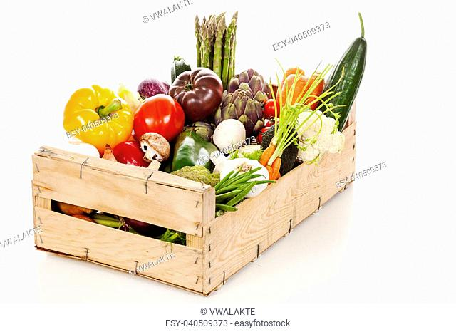Assortment of fresh vegetables in a crate on white background