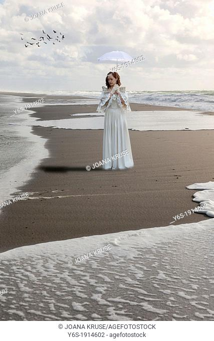 a woman in a victorian dress is walking along the shore of the sea