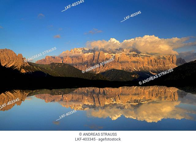 Sella range reflecting in a mountain lake, Val Gardena, Dolomites, UNESCO world heritage site Dolomites, South Tyrol, Italy