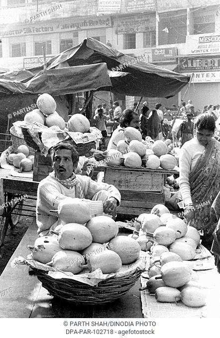Vegetable vendor market  Varanasi  Uttar Pradesh  India agrarian products bazaar Black & White B/W buildings buyers buying display fruits India man men Market...