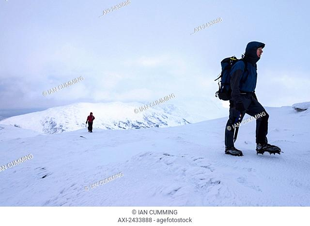 Woman and man walking up Beinn Dorain in snowy, winter conditions, near Bridge of Orchy; Argyll and Bute, Scotland