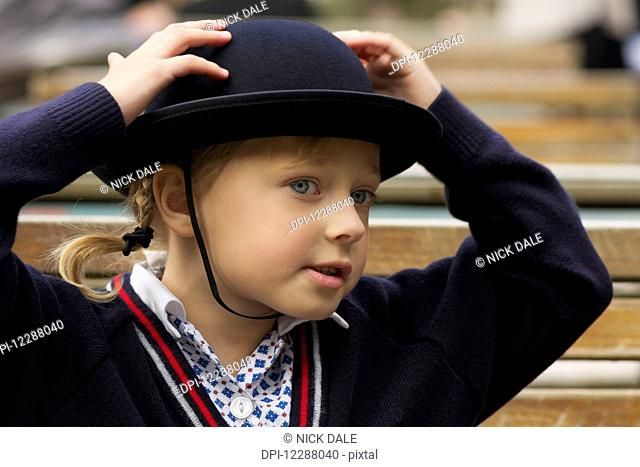 Young girl with her hands on her blue felt hat wearing school uniform; London, England