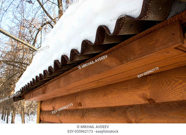The snow on the roof of a wooden house
