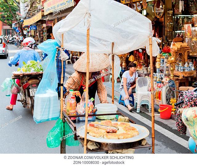 vietnamesische Straßenverkäufer handeln und verkaufen ihre Gemüse und Obst Waren in Hanoi, Vietnam Vietnamese street vendors act and sell their vegetables and...