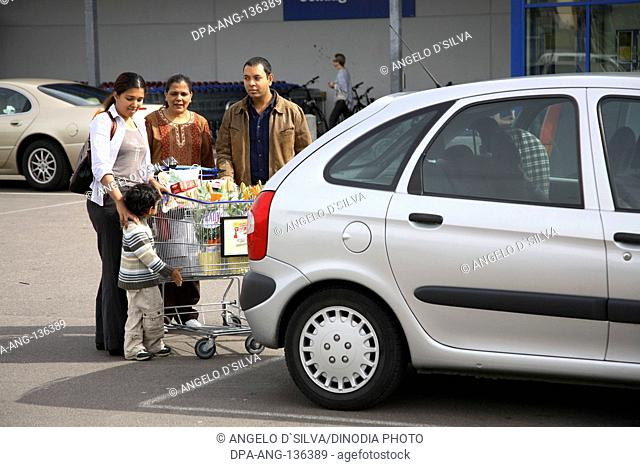 Family keeping consumable items from trolley to car boot ; Sweden MR468
