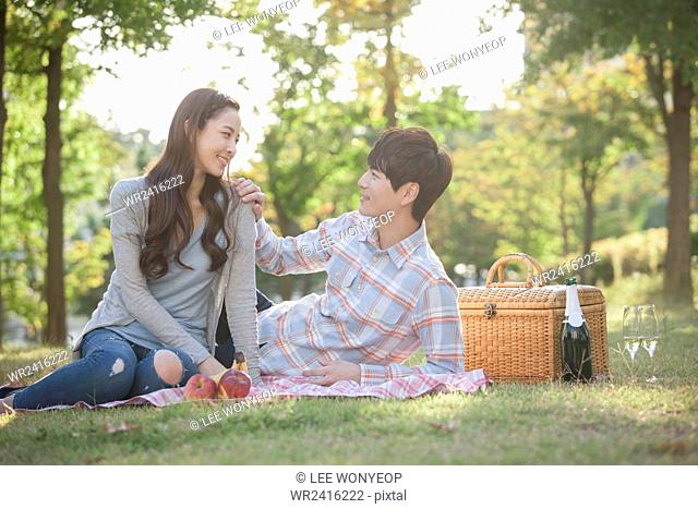 Couple on a picnic and looking at each other with a smile at park