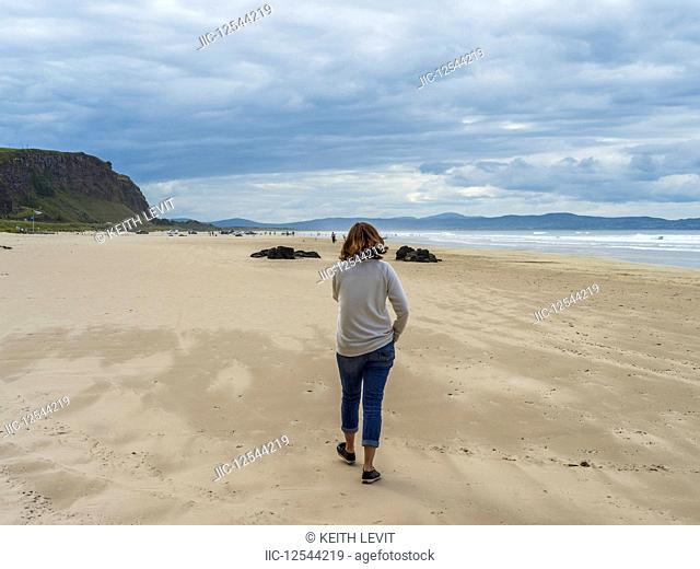 Woman walking on Downhill Beach, Northern Ireland; Castlerock, County Londonderry, Ireland