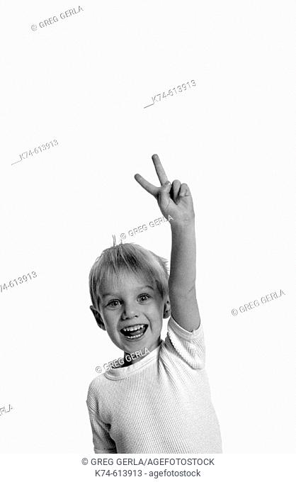 image of young boy making a peace sign with his fingers