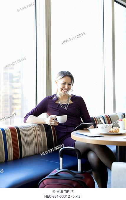 Businesswoman using digital tablet and drinking coffee at breakfast in airport lounge